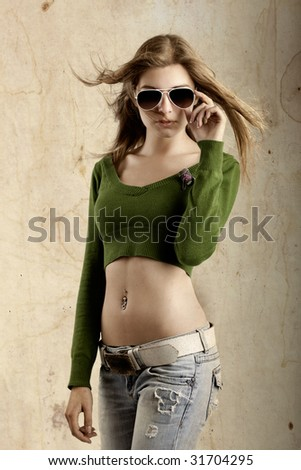 Beautiful young fashion model over a grunge background - stock photo
