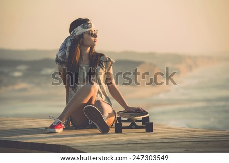 Beautiful young fashion skater girl looking at the sunset - stock photo
