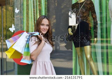 Beautiful young fashion woman holding shopping bags and standing near shop window - stock photo