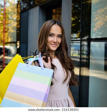 Beautiful young fashion woman holding shopping bags and standing near shop window, toned - stock photo