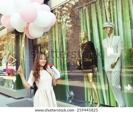 Beautiful young fashion woman holding shopping bags and standing near shop window, toned - stock photo