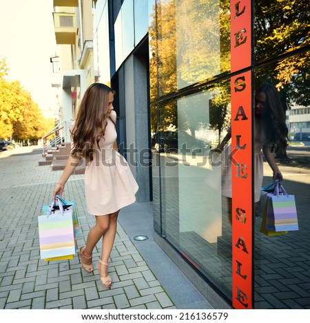 Beautiful young fashion woman with shopping bags looking at shop window - stock photo