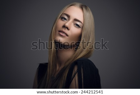Beautiful young fashionable girl on a gray background. Fashion makeup - stock photo
