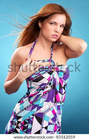 Beautiful young fashionable woman over blue background - stock photo