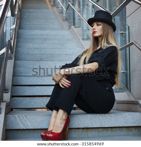 Beautiful young fashionable woman posing in black suite, red shoes with high heels and black hat. Vogue style. Urban background - stock photo