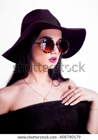 Beautiful young fashionable woman posing in dress and black hat. Vogue style.expressive young model with hat and sunglasses.Beautiful woman in hat. Retro fashion.studio portrait - stock photo