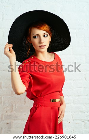 Beautiful young fashionable woman posing in red dress and black hat. Vogue style - stock photo