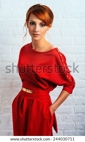 Beautiful young fashionable woman posing in red dress. Looking at camera. Vogue style  - stock photo
