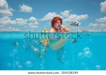 Beautiful young fat woman is swimming with yellow duck lifebuoy and defending oneself against flock of piranhas  - stock photo