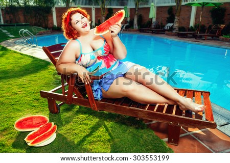 Beautiful young fat woman relaxing on deck chair by the pool