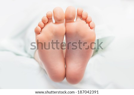 Beautiful young feet with body cream - stock photo