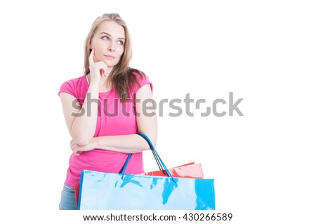 Beautiful young female at shopping holding colorful paper bags and thinking what to buy isolated on white with copyspace - stock photo