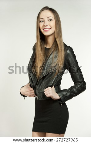 Beautiful young female brunette with straightened hair laughing and smiling in a studio setting while wearing a leather jacket and a short black cut dress on a white background. - stock photo
