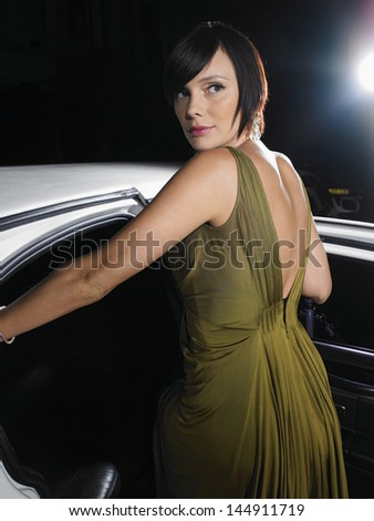 Beautiful young female celebrity in evening wear getting into limousine