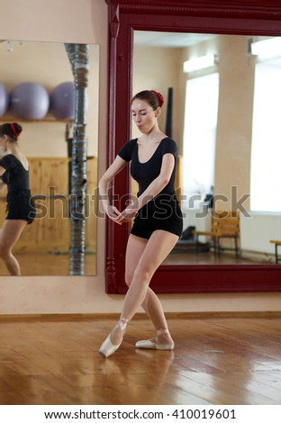 Beautiful young female classical ballet dancer on pointe shoes wearing a black leotard and shorts in class classical dance against mirror.Ballet/ posing in fitness center on a studio mirror background