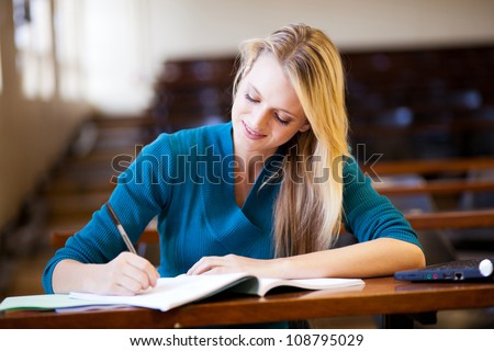 beautiful young female college girl sitting in lecture room - stock photo