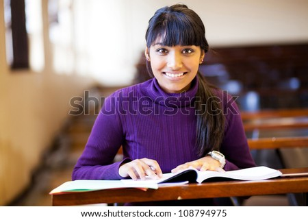 beautiful young female college student in classroom - stock photo