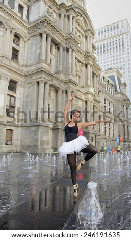Beautiful young female dancer (classical ballet) or ballerina dances en pointe among small fountains outside of stone building - wearing a white tutu and black bodice  - stock photo