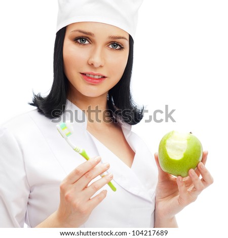 Beautiful young female dentist doctor with a toothbrush and green apple. Dental care concept - stock photo