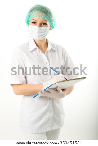 beautiful young female doctor in medical gown and rubber gloves holding a medical records. nurse making entries in medical records - stock photo