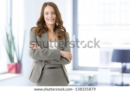 Beautiful young female executive businesswoman smiling in her office - stock photo