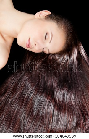 beautiful young female face with long beauty hair over black