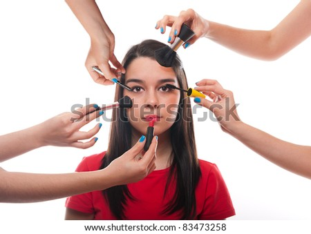 Beautiful young female getting her make-up done - stock photo