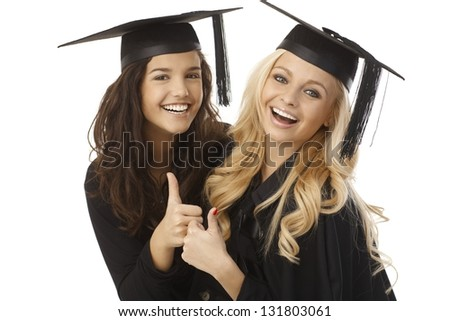 Beautiful young female graduates in square academic cap showing ok sign, hugging, smiling happy. - stock photo
