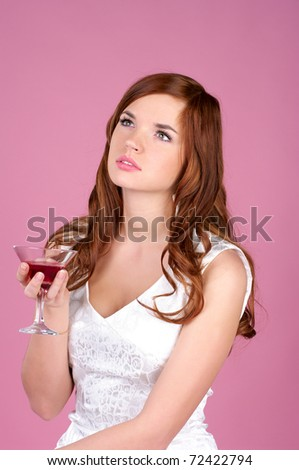 Beautiful young female in evening gown with cocktail in hand - stock photo