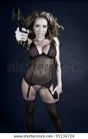 Beautiful young female in sexy lingerie holding a hand gun - stock photo