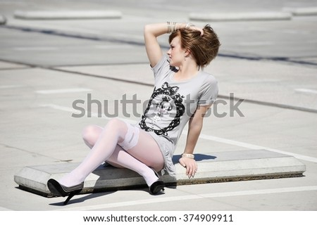 Beautiful young female in summer dress siting on the ground, attractive woman posing to the camera, cute girl with sexy body siting outdoors. - stock photo