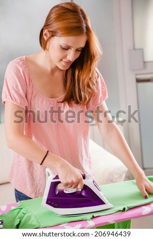 Beautiful Young Female Ironing Clothes - stock photo