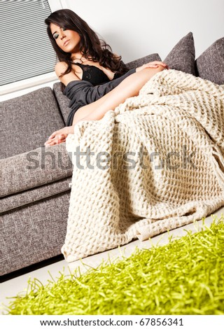 Beautiful young female lying at sofa, covered with blanket - stock photo