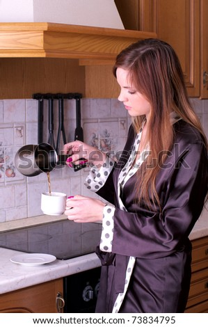 Beautiful young female make coffee at the home kitchen - stock photo