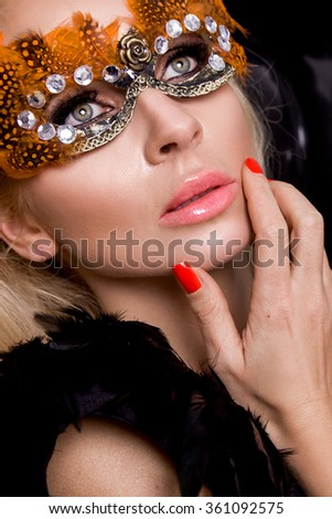 beautiful young female model in a carnival mask with feathers standing against the black balloons and sensually looks at the camera, wearing ball gowns prom evening dress with mesh and amazing makeup