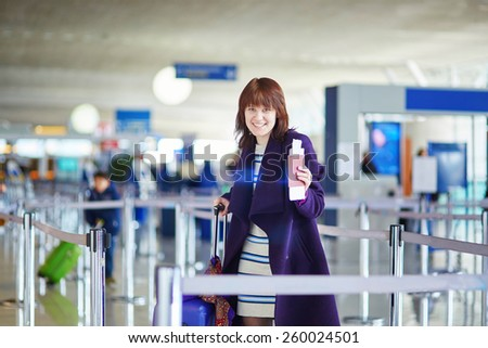 Beautiful young female passenger at the airport - stock photo