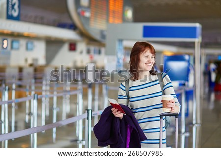 Beautiful young female passenger at the airport with take away coffee