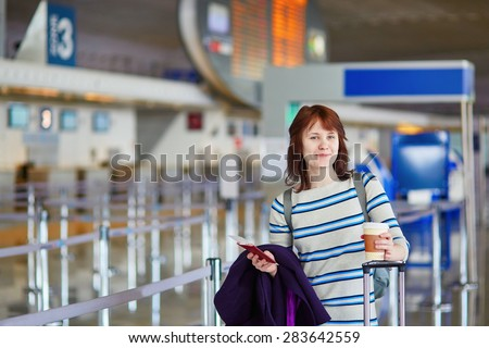 Beautiful young female passenger at the airport with take away coffee, walking through the arrival or departure hall