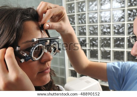 Beautiful young female patient having a medical examination at optician - a series of eye exam related pictures. - stock photo