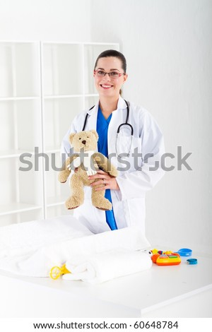 beautiful young female pediatrician in office - stock photo