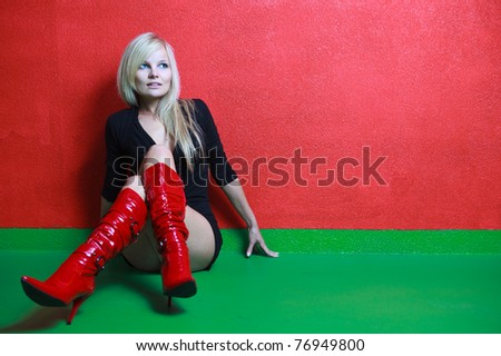 Beautiful young female photo model wearing high red boots posing in front of a red wall - stock photo