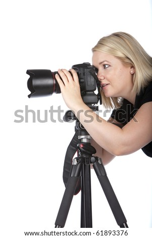 Beautiful Young Female Photographer Taking a Photo with Camera on a Tripod - stock photo