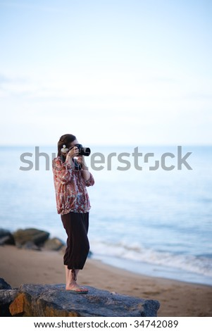 Beautiful young female photographer taking pictures on beach - stock photo