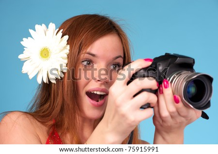Beautiful young female photographer with white flower in hair - stock photo