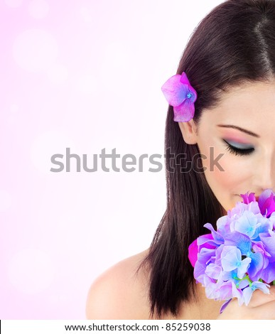Beautiful young female portrait, hand holding a purple flower, isolated on pink background, beauty and spa concept - stock photo