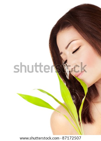 Beautiful young female portrait, holding green leaves plant, isolated on white background with white text space, beauty and spa concept - stock photo