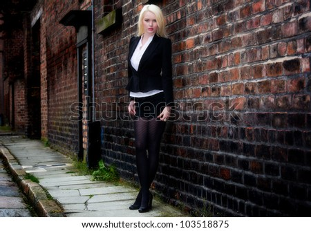 Beautiful young female posing against brick wall - stock photo