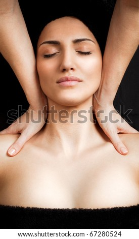 Beautiful young female receiving shoulder massage in spa, relaxed - stock photo