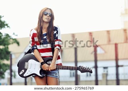 Beautiful young female rock guitarist outdoor  - stock photo