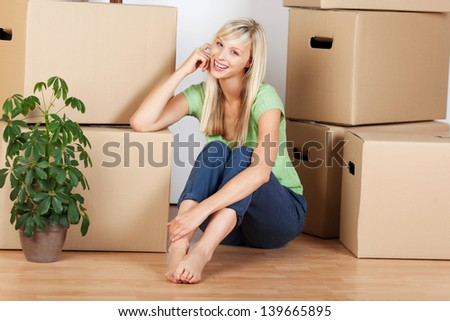 Beautiful young female sitting next to boxes in new house